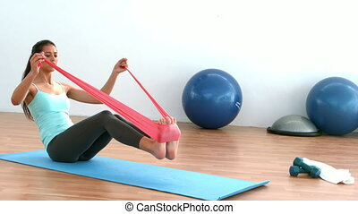 Fit brunette stretching using resitance band in studio in...
