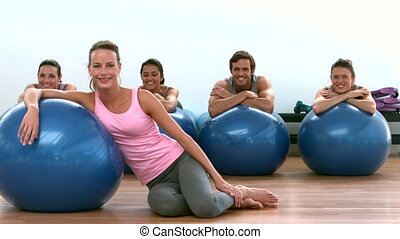 Fitness class smiling at camera with exercise balls in slow...