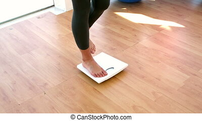 Woman stepping on scales in slow motion