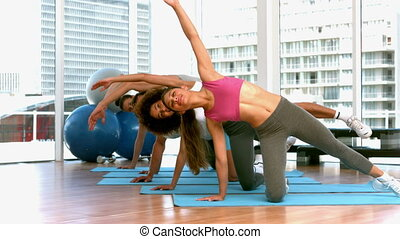 Fitness class doing yoga on exercis