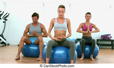 Fitness class doing yoga on exercise balls