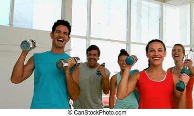 Fitness class smiling at camera wi