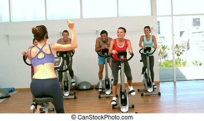 Spin class working out with instructor in slow motion