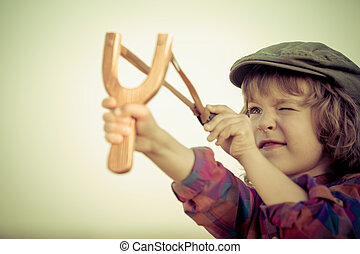 Kid holding slingshot in hands against summer sky...