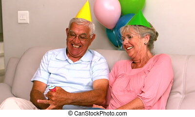 Senior couple celebrating a birthday on the couch in slow...
