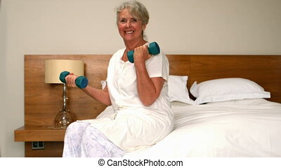 Senior woman lifting dumbbells in bedroom in slow motion