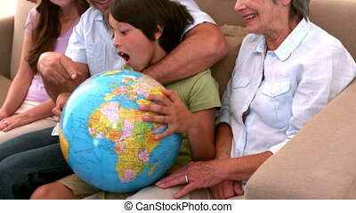 Extended family looking at globe together on couch in slow...