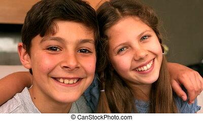 Siblings smiling at camera