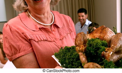 Grandmother holding roast chicken in front of family in slow...