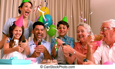 Extended family celebrating birthday together on couch in...