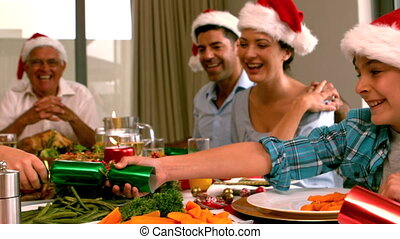 Siblings pulling a christmas cracker at the dinner table in...