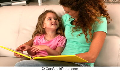Mother and daughter reading book on the couch in slow motion