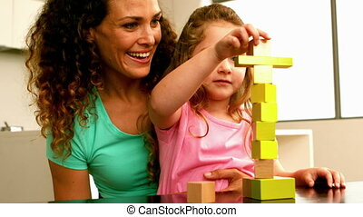 Mother playing with daughter with blocks in slow motion