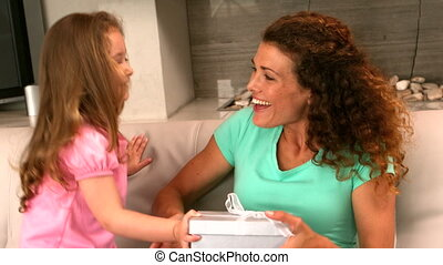 Little girl giving a gift to her m - Little girl giving a...