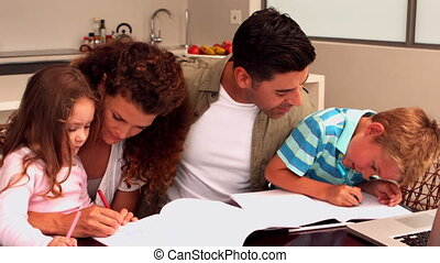Parents colouring with their children at the table in slow...