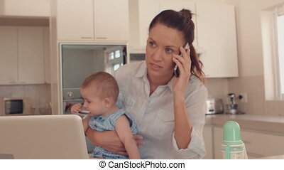 Mother holding baby and talking on phone in slow motion