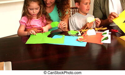 Parents and children making paper shapes together at the...