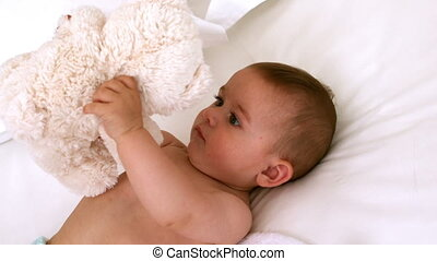 Cute baby on a bed with teddy bear in slow motion