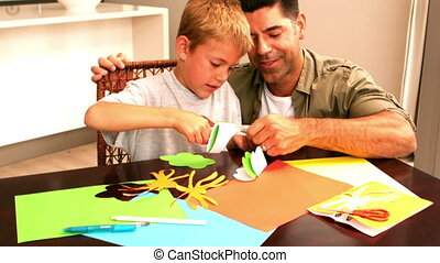Father and son making paper shapes together at the table in...