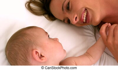 Cute baby on a bed with mother in slow motion