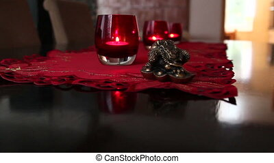 Two red glasses with candles on top of a table and a mat on...