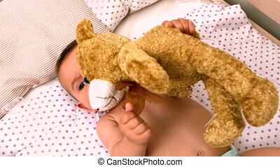 Baby lying in crib sucking soother holding teddy in slow...