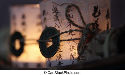 A candle in a glass wrapped in paper with chines characters...