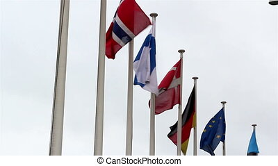 Flags of different nations are waving so fast on the pole -...
