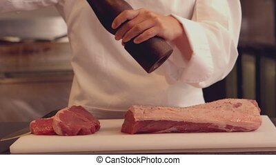 Chef seasoning a piece of beef in slow motion