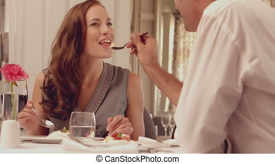 Man feeding his brunette wife in slow motion