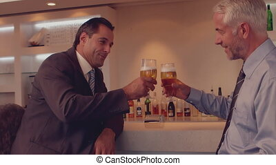 Businessmen having a beer together in slow motion