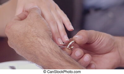 Man placing ring on womans finger in slow motion