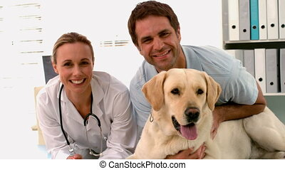 Vet with dog and dog owner smiling at camera in slow motion
