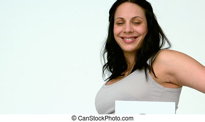 Pregnant woman holding question mark over her belly in slow...
