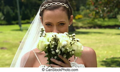 Bride smelling her bouquet in the park in slow motion