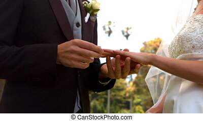 Man placing ring on brides finger in slow motion