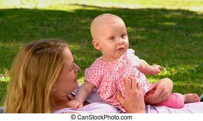 Mother lying with her baby girl in the park in slow motion