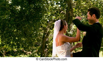 Happy newlywed couple dancing in the park in slow motion