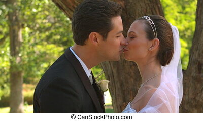 Newlyweds kissing in the park