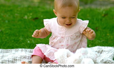 Happy baby laughing in the park on the blanket in slow...