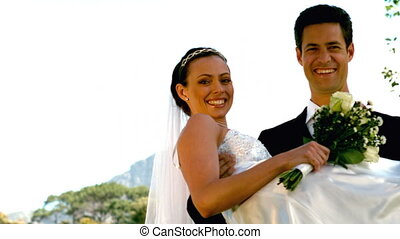 Happy newlywed couple in the park in slow motion