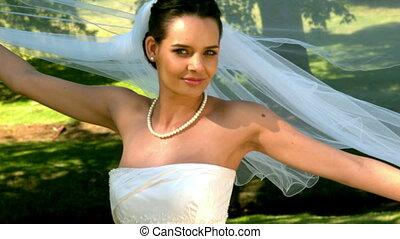 Bride posing for camera in the par - Bride posing for camera...