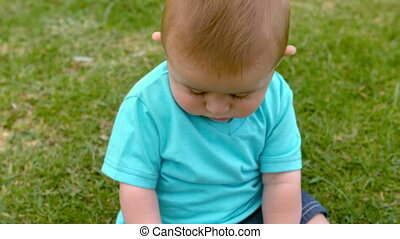 Cute baby sitting on the grass in slow motion