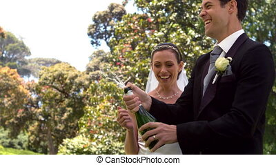 Groom popping bottle of champagne with new wife in slow...