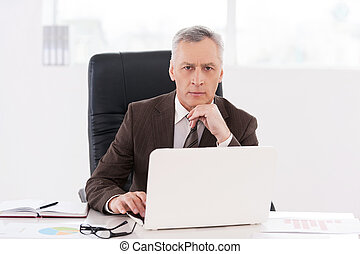Confident businessman. Confident senior man in formalwear working on laptop and looking at camera while sitting at his working place