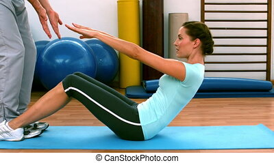 Woman doing sit ups with her traine