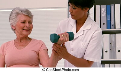 Physiotherapist helping patient lift hand weight in slow...