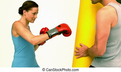 Fit woman punching a bag held by trainer in slow motion
