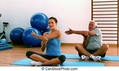 Elderly man sitting on mat exercising with instructor in...