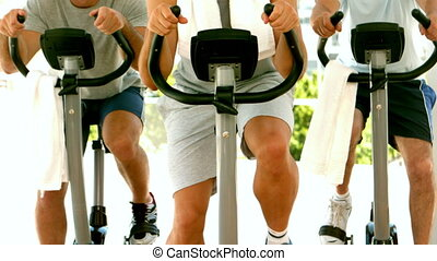 Group of men in fitness studio on exercise bikes in slow...